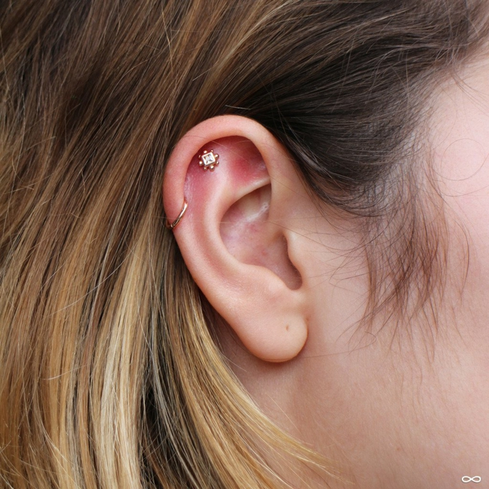 woman with blonde hair, close up photo, triple helix piercing, two golden earrings
