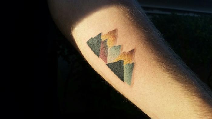 minimalist tattoo, forearm tattoo, colored mountain range, mountain tattoo, orange blue black and red colors