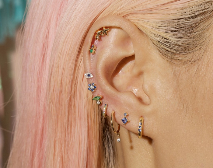 woman with blonde pink hair, wearing multiple different earrings, triple helix piercing, colorful rhinestones