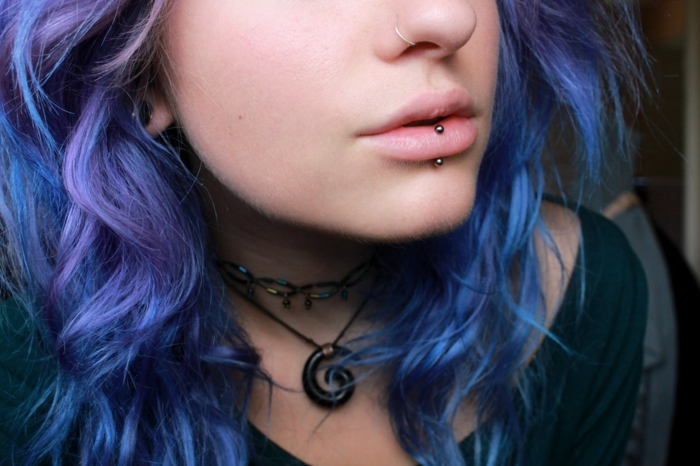 woman with blue and purple hair, labret piercing, nose ring piercing, wearing black blouse