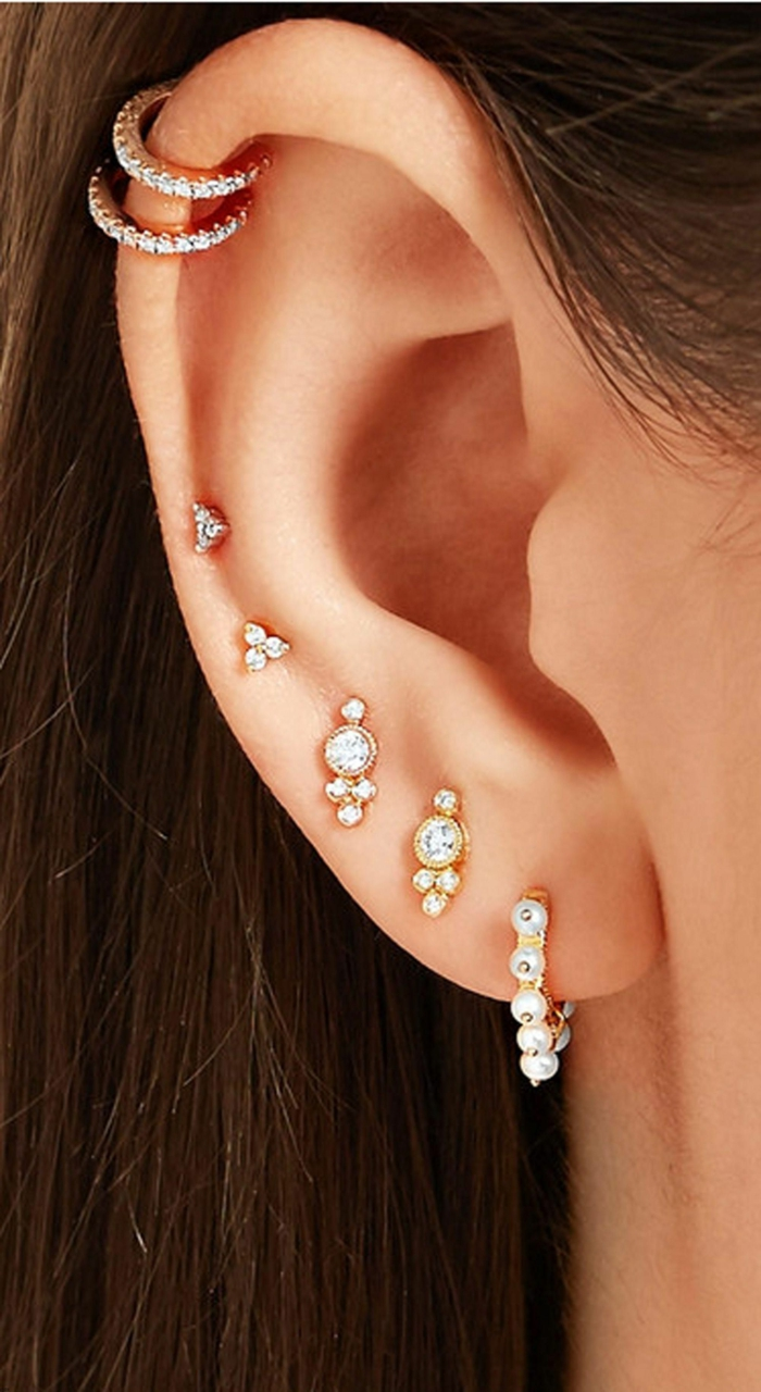 multiple earrings with rhinestones, close up photo of an ear, triple helix piercing, woman with brown hair