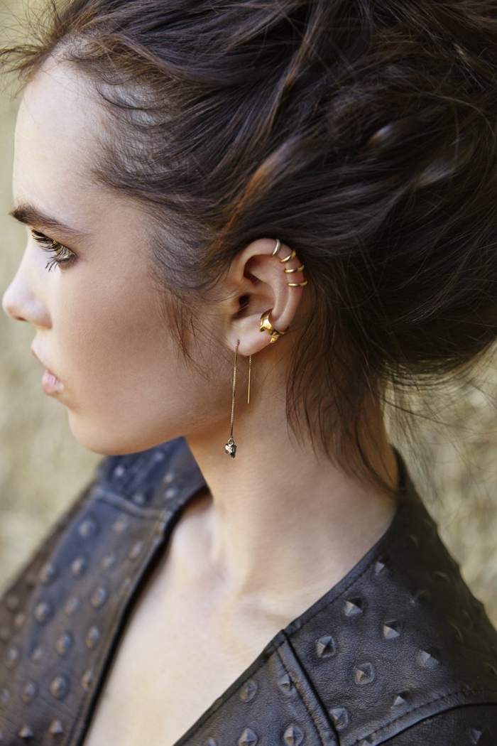 woman with brown hair, wearing black leather jacket, helix piercing, multiple golden earrings on her ear