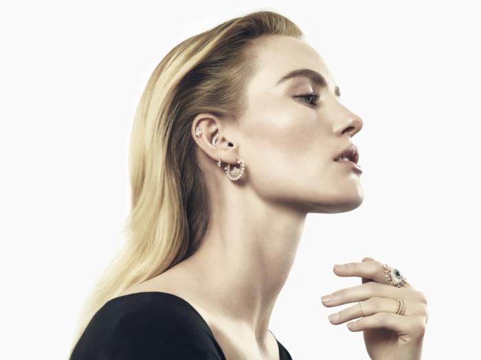woman with blonde hair, wearing black top, triple helix piercing, multiple earrings with rhinestones