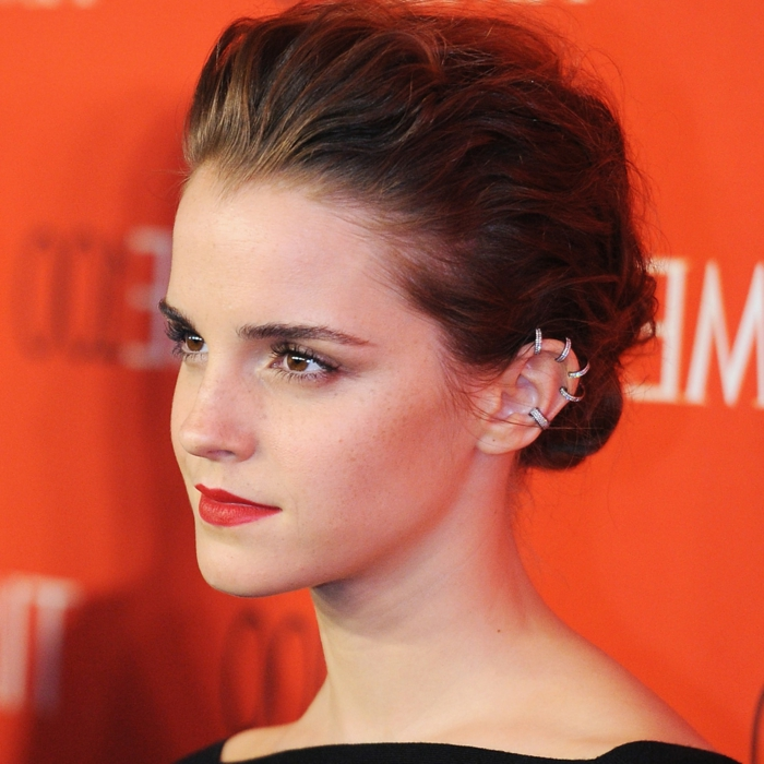 emma watson, brown hair in low updo, helix piercing, red lipstick, multiple ring earrings with rhinestones