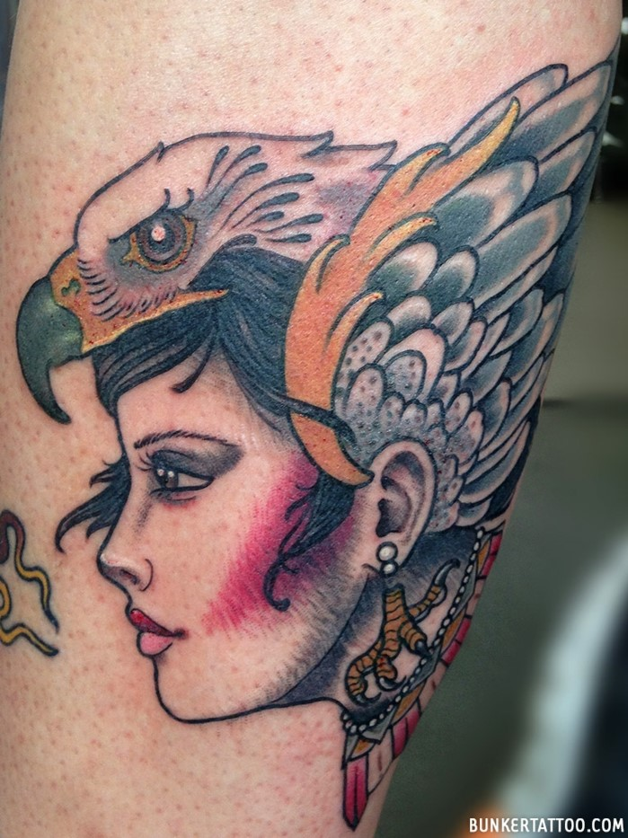 woman with black hair, falcon on her head, traditional tattoo designs, leg tattoo