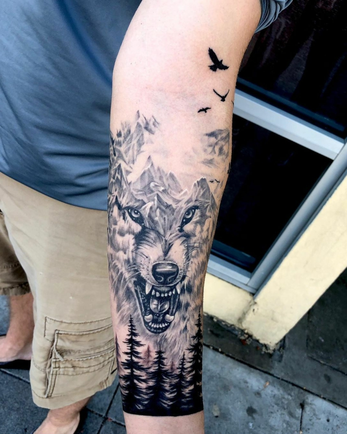 forearm tattoo, wolf head as a mountain range, trees underneath, mountain tattoo, birds flying