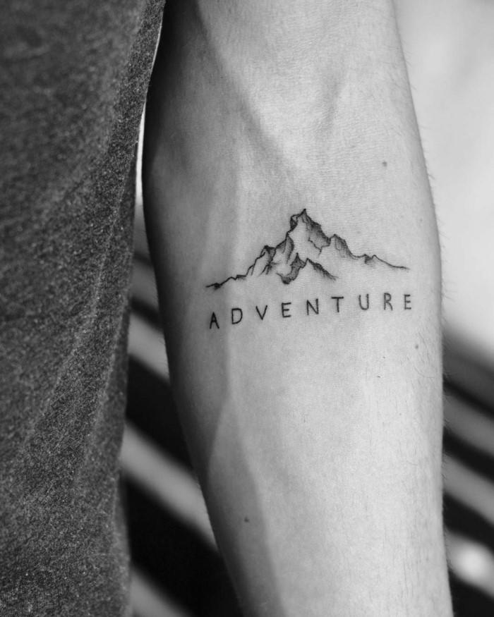 adventure written underneath mountain range, mountain tattoo, forearm tattoo, black and white photo