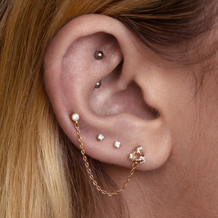 woman with blonde hair, close up photo of an ear, hoop cartilage piercing, multiple gold earrings with rhinestones