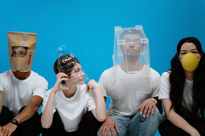 four people with different things placed on their heads, diy face mask for breathing, blue background