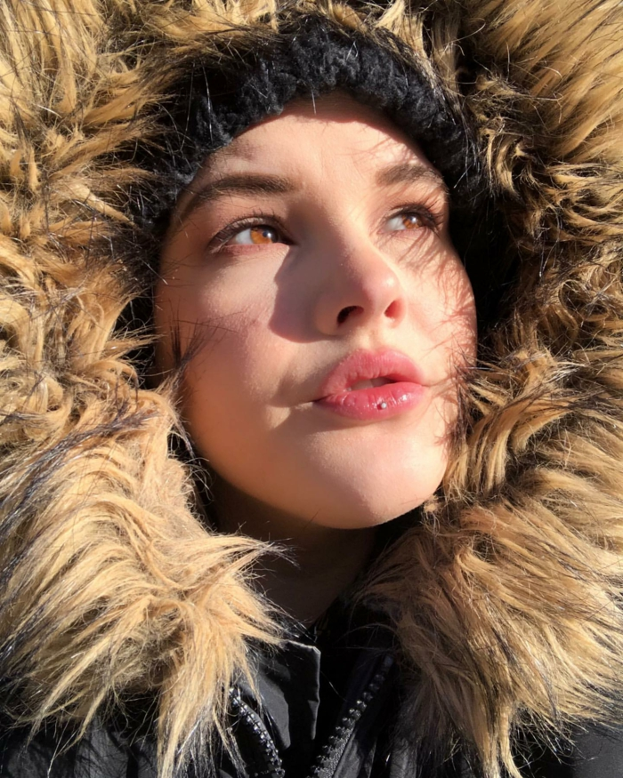 girl with brown eyes, ooking up at the sun, wearing a large hood, labret piercing, black beanie