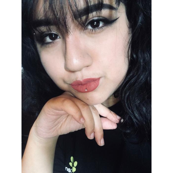 girl with black hair with bangs, pink matte lip gloss, horizontal lip piercing, black eyeliner