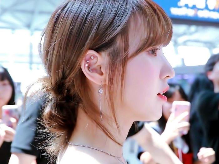 woman with brown hair in a low updo, wearing multiple earrings with rhinestones, hoop cartilage piercing