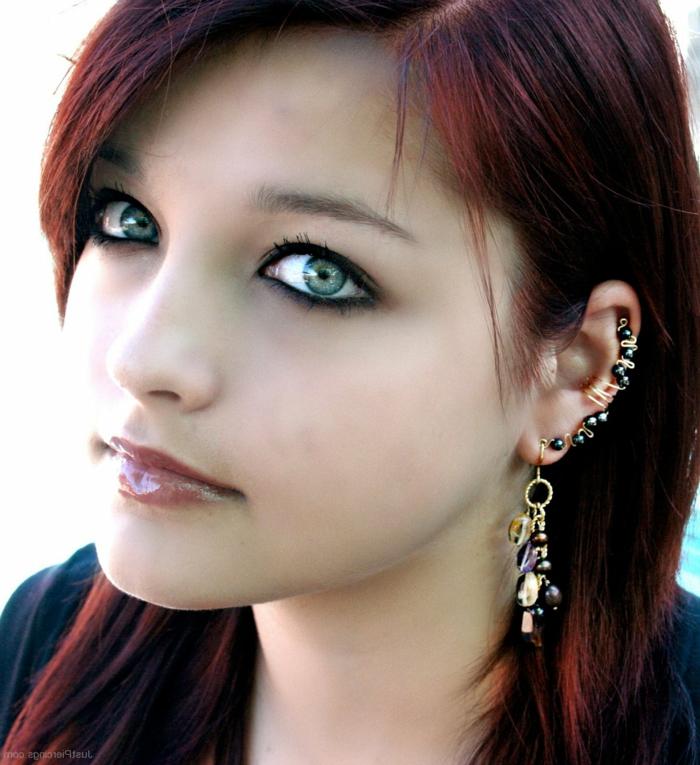 woman with red hair and green eyes, hoop cartilage piercing, wearing multiple earrings with black rhinestones