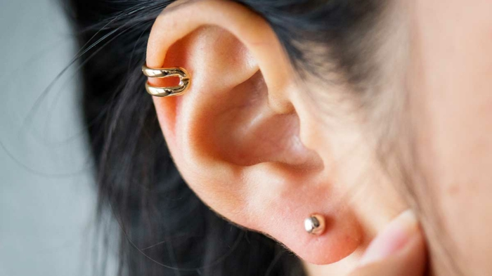 close up photo of an ear, hoop cartilage piercing, woman with black hair, gold ring earrings