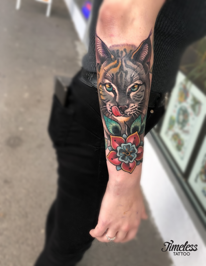 neo traditional animal tattoo, forearm tattoo, half tiger half cat face with red flower underneath
