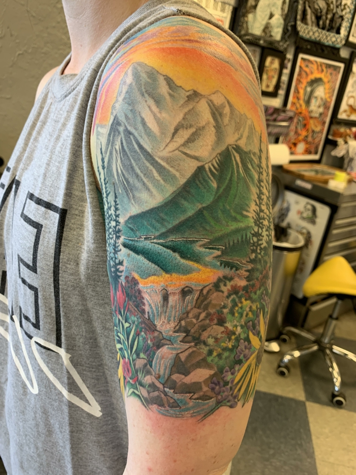 watercolor shoulder tattoo, hiking tattoos, lake surrounded by trees and flowers, mountain range in the background
