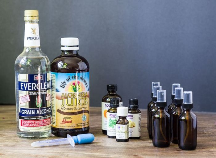 diy hand sanitizer, bottles of grain alcohol and aloe vera juice, small spray bottles of essential oil