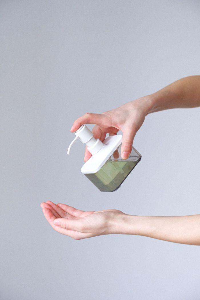 plastic bottle full of antibacterial gel, hand sanitizer, sprayed on female hand, white background