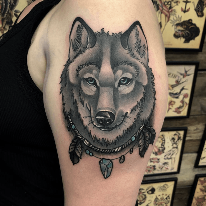 black and grey tattoo, wolf face with necklace with feathers, neo traditional animal tattoo, blue eyes