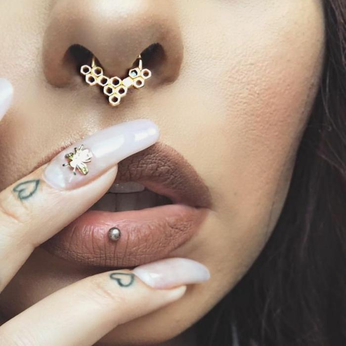 close up photo, woman wearing nude matte lip gloss, ashley lip piercing, honeyvomb septum ring piercing