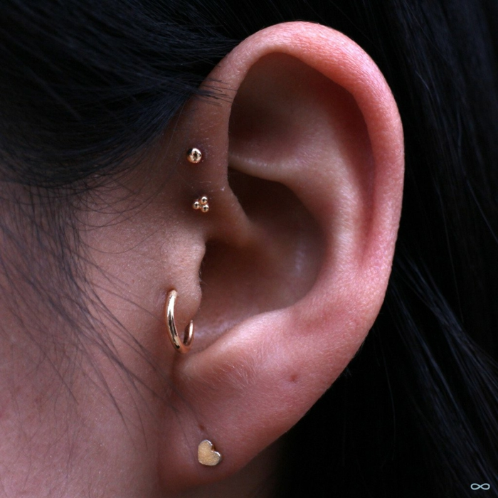 cartilage piercing earrings, close up photo of an ear, woman with black hair, wearing multiple stud earrings