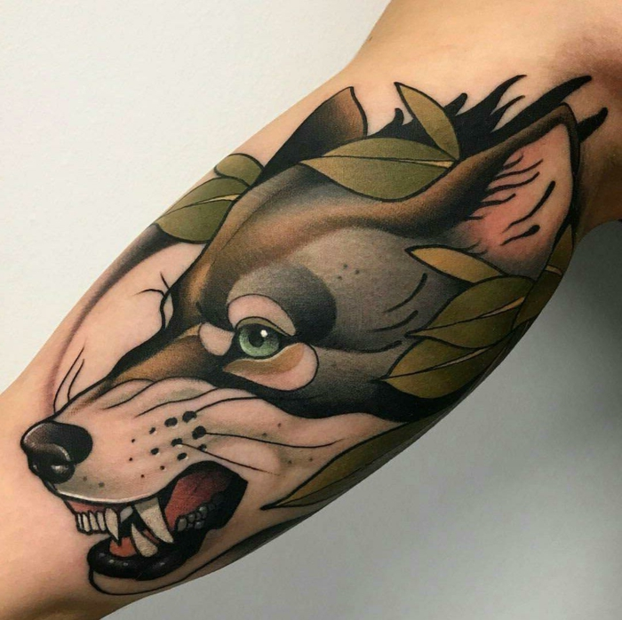growling wolf head, surrounded by green leaves, what is a neo traditional tattoo, inside arm tattoo