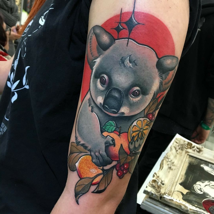 koala holding fruits, red background behind it, neo traditional rose tattoo, arm tattoo