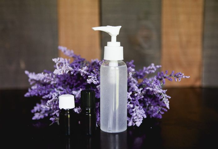 bouquet of lavender, two small bottle of essential oil, hand sanitizer, large plastic spray bottle