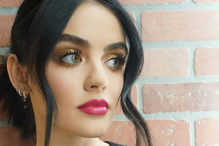 lucy hale, black hair in a low updo and green eyes, cartilage piercing earrings, red lipstick