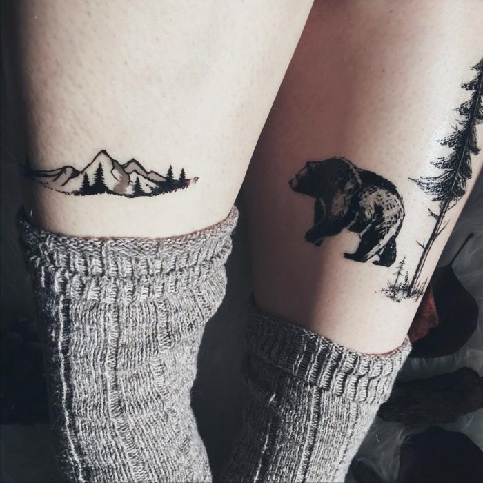 leg tattoos, mountain range on one leg, bear and tall tree on the other, mountain tattoo, grey socks