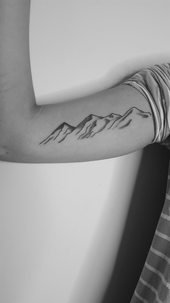 black and white photo, simple mountain tattoo, mountain range on the inside of the arm