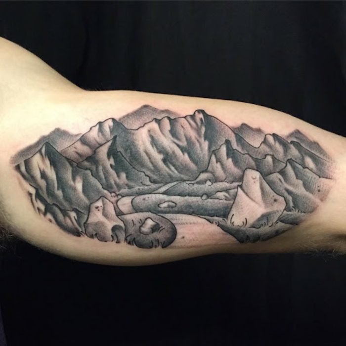 inside the arm tattoo, minimalist mountain tattoo, road between mountain peaks, black background