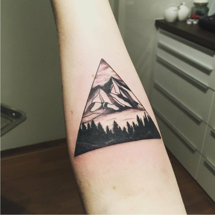 forearm tattoo, minimalist mountain tattoo, mountain range next to lake, surrounded by trees inside a triangle