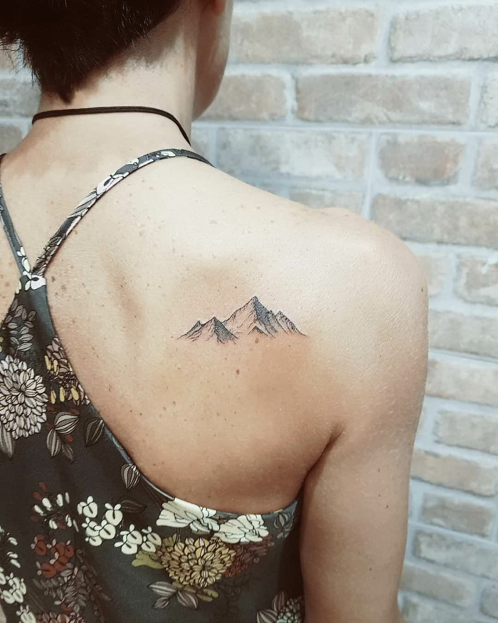 back of shoulder tattoo, minimalist mountain tattoo, woman wearing floral top, brick wall in the background