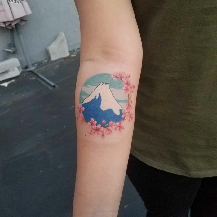 mountain with snowy peak, blue sky inside a circle, surrounded by cherry blossoms, mountain tattoo ideas, watercolor forearm tattoo