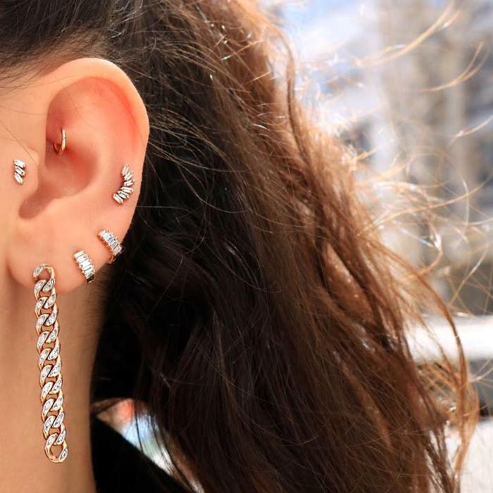 woman with brown wavy hair, wearing multiple earrings with rhinestones, stud cartilage piercing