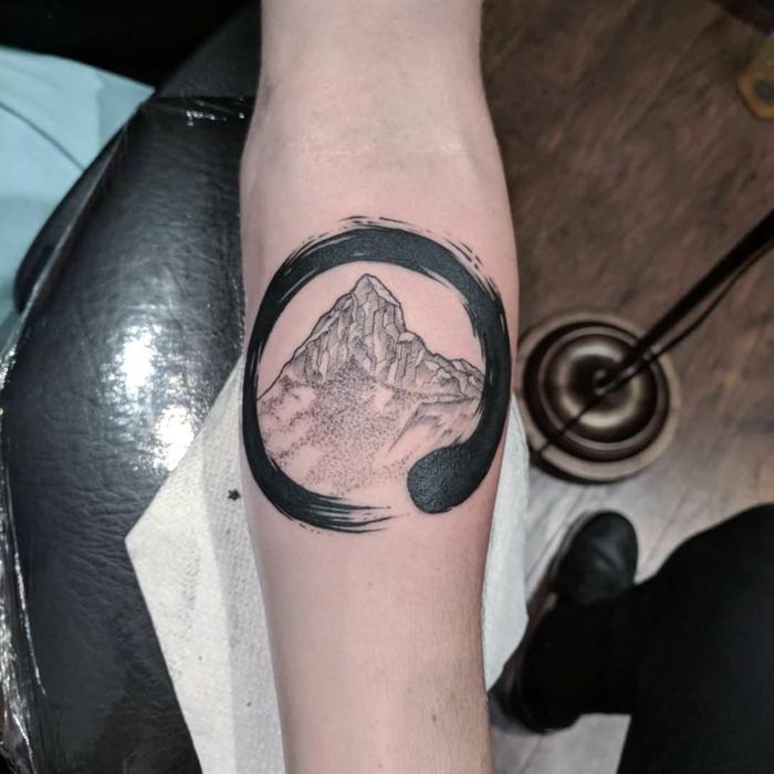 ouroboros symbol around a mountain range, mountain tattoo ideas, forearm tattoo