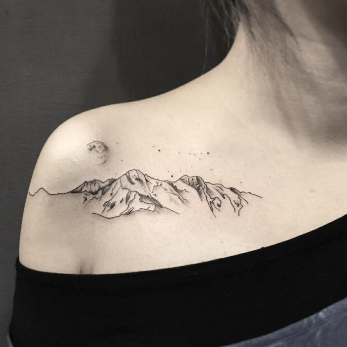 shoulder tattoo, mountain range with moon above it, mountain scene tattoo, woman wearing black blouse