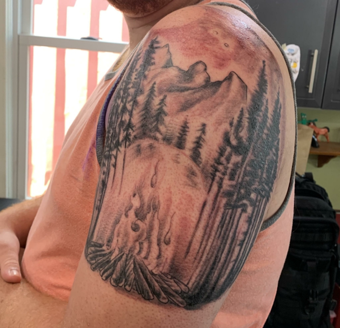 watercolor shoulder tattoo, mountain scene tattoo, camp fire burning between trees, mountain in the background