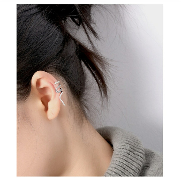 woman with black hair in a bun, wearing snake like silver earring with rhinestones, how long does a cartilage piercing take to heal