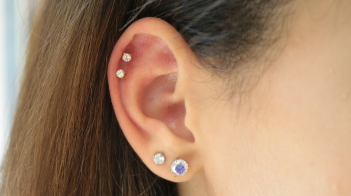 woman with brown hair, how long does a cartilage piercing take to heal, close up photo of an ear, earrings with rhinestones