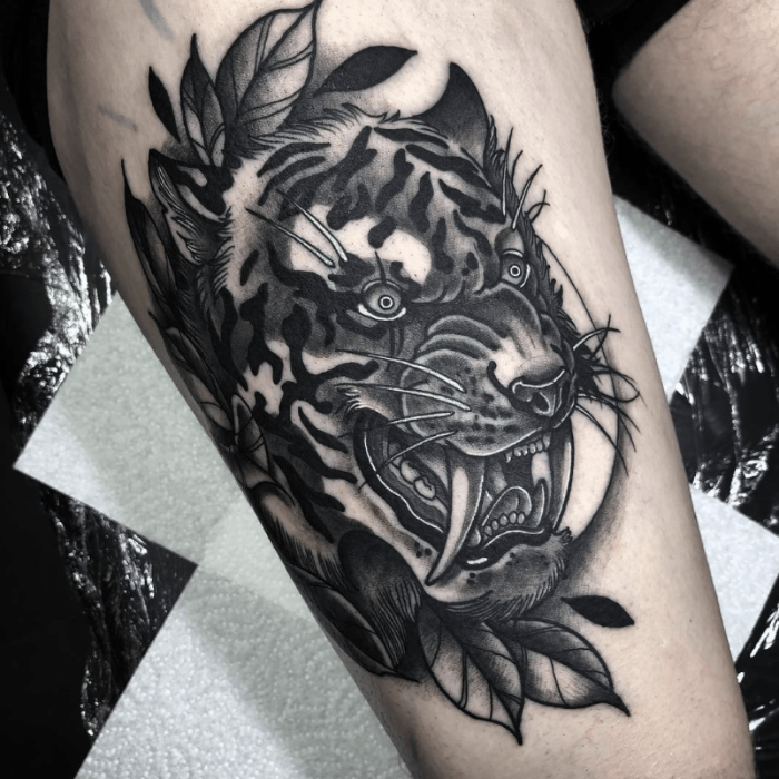 black and grey tattoo, thigh tattoo, growling tiger head with large teeth, traditional forearm tattoo