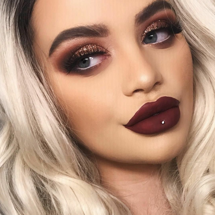 blonde woman with blue eyes, bottom lip piercing, dark red burgundy matte lip gloss, glitter eyeshadow