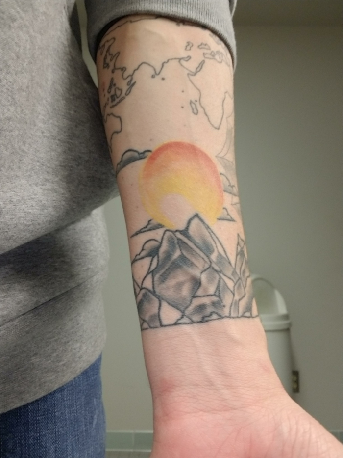 watercolor sun in yellow and orange, over a mountain range, mountain tattoo meaning, forearm tattoo