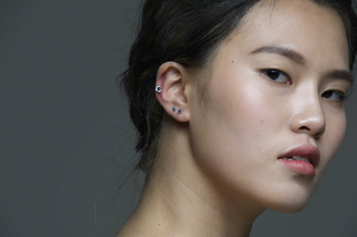 woman with black hair in a low updo, how much is a cartilage piercing, wearing earrings with blue rhinestones