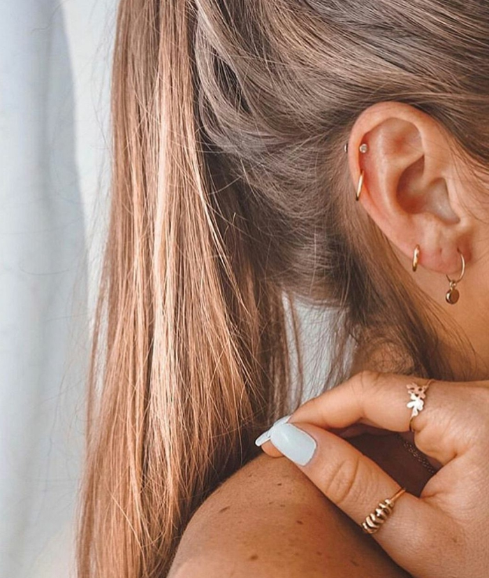 how to clean cartilage piercing, woman with blonde hair in a ponytail, wearing multiple different gold earrings