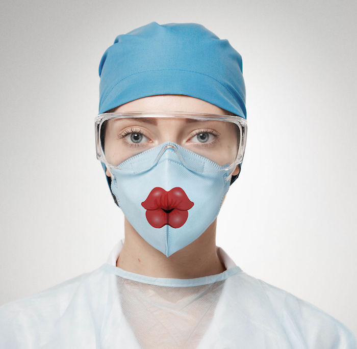 woman with blue eyes, wearing a face mask with lips prnted on it, diy breathing mask, surgical hat and goggles