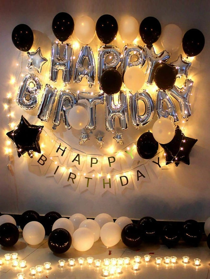 silver happy birthday balloons, surrounded by fairy lights, gifts for 18 year old boys, black and white balloons