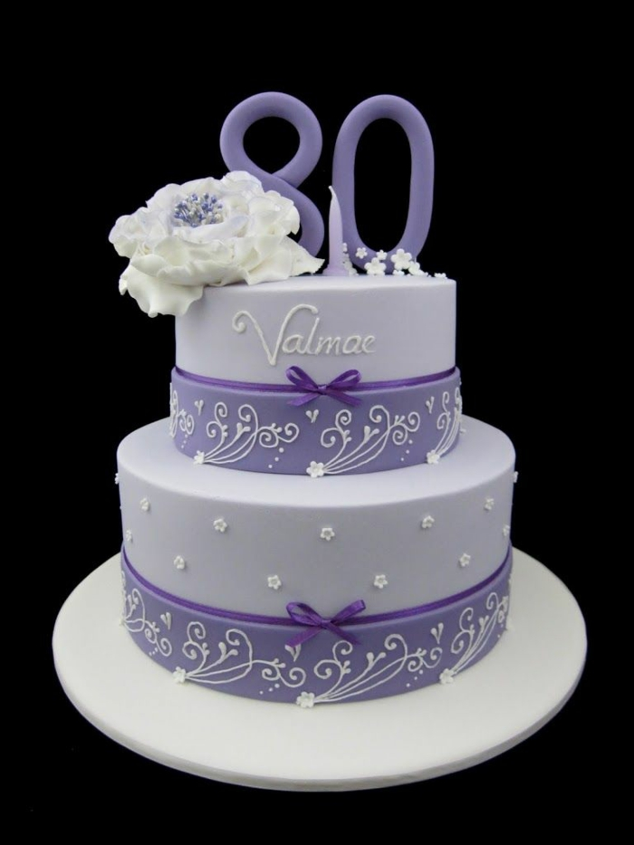 two tier cake, covered with purple fondant, 80th birthday ideas for mom, decoated with white flower