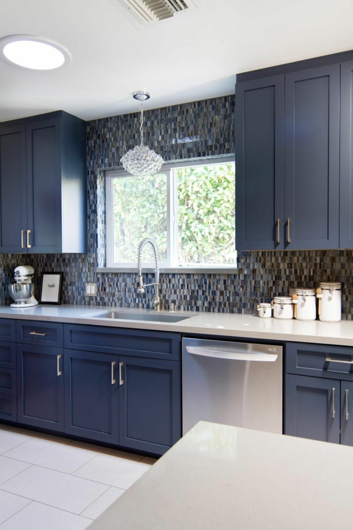 black cabinets with white countertop, modern kitchen cabinets, grey mosaic backsplash, white tiled floor